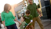 A family of four walks in the Downtown Disney area during the St. Patrick's Week celebration