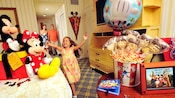 A little girl rushes ahead of her parents into their resort room welcoming her with Disney presents