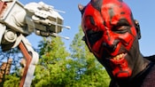 A smirking Darth Maul with an AT-AT Walker in the background at Star Wars Weekends at Disney's Hollywood Studios