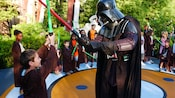 Darth Vader and a young Jedi student engaging in a Lightsaber battle as other young students watch