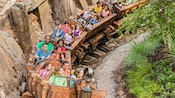 Excited Guests of all ages smile on a ride aboard the Seven Dwarfs Mine Train at Magic Kingdom park