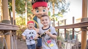 A duo of young boys holding spyglasses during a 'Jake and the Never Land Pirates' Character Greeting