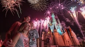 A mother, daughter and son all watch in wonder while fireworks explode high above Cinderella Castle