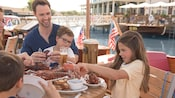 At a waterfront restaurant a girl shucks a lobster while her mother, father and 2 brothers watch
