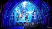 Guests in a boat look on as Princess Elsa perfects her ice palace