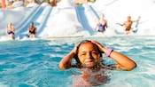A smiling little girl comes up for air after finishing a ride on a water slide