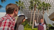 A Disney Tour Guide points out the Spaceship Earth sphere at Epcot to a young man and woman Guest.