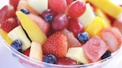 A bowl of freshly prepared strawberries, blueberries, pineapple, watermelon, peaches and grapes