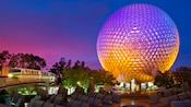 A cascade of sunset hues colors Spaceship Earth as it extends into the evening sky above Epcot
