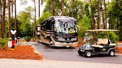 A golf cart and a bus parked at a campsite in the woods at The Campsites at Disney's Fort Wilderness Resort