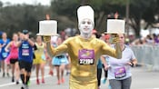 A runner in a road race who is dressed as the Beauty and the Beast character Lumiere wears a lamé body suit, carries a replica candlestick in each hand and wears white face paint and a hat on his head resembling a third candlestick