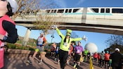 A man wearing a Goofy hat with long ears and padded white gloves strikes a celebratory pose as he leads a group of runners through Epcot as a monorail passes overhead