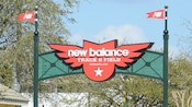 A large sign bearing the inscription New Balance Track & Field Complex is supported between two posts, each of which is topped with a replica metal flag with the New Balance logo
