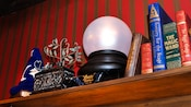 A shelf with books, a crystal ball and a sorcerer hat