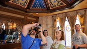 Guests admire a room reminiscent of a castle as one prepares to photograph the decorative ceiling