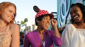 A woman in a polka dot Minnie Mouse cap smiles along with 2 female friends