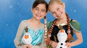 2 smiling girls wearing Anna and Elsa costumes from the Disney film Frozen, holding Olaf plush toys