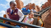 A VIP Tour Guide rides with a young female Guest while they both enjoy Big Thunder Mountain Railroad