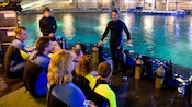 2 scuba instructors providing instructions to divers before a dive