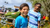Young Guests smile while standing in front of a topiary display themed to the Disney•Pixar film Cars