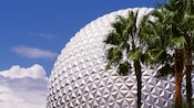 Palm trees sway in the wind as Spaceship Earth rises high into the cloudy Florida sky at Epcot