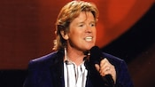 Peter Noone of Herman's Hermits holding a microphone while performing on stage