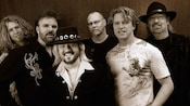 Band members from 38 Special standing together while adorned in country-style wear and cowboy hats