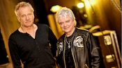 Band members from Air Supply standing together in a stadium hallway filled with tour equipment
