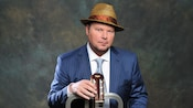 Musician Christopher Cross standing straight-faced with his hands in the pockets of a pin-striped suit