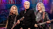 Musician Dennis DeYoung of the rock band Styx singing excitedly into a microphone