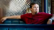 Singer Edwin McCain pensively staring out the window while sitting in a booth at a diner