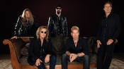 Band members from Night Ranger sitting and standing together while dressed in dark leather and denim