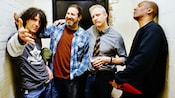 Band members from The Spin Doctors goofing around together in a brick hallway