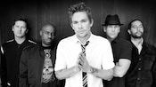 Mark McGrath and band members from Sugar Ray standing together against a wooden wall