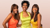 Members of the all-female group The Pointer Sisters smiling together while wearing bright dresses