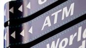 Directional signs that resemble film, one with arrows and the letters 'ATM'