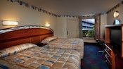 2 double beds with a long curved headboard spanning both beds opposite a flat-screen TV and adjacent to a window