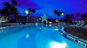 A pool lit up after dark at Disney's All-Star Sports Resort