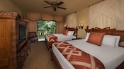 2 queen beds with curtained headboards, ceiling fan, flat-screen TV and dresser, curtained balcony