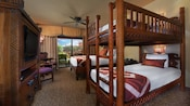 Carved wood bunk beds, flat-screen TV in wood chest, queen bed, chairs, curtained balcony