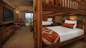 Carved wood bunk beds, TV in wood chest, queen bed, chairs, ceiling fan, curtained balcony