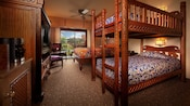 Bunk beds next to a queen bed across from a TV armoire