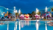 Big Blue Pool lit up at night, featuring giant jellyfish and Crush the turtle at Disney's Art of Animation Resort
