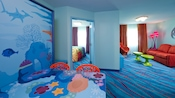 A Finding Nemo-themed table/bed and, in the background, a bedroom next to a living room