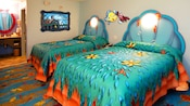 2 Little Mermaid-themed double beds with a vanity area in the background