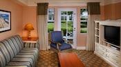 Mesa auxiliar, silla acolchada, lámpara, cuadro, cajones del armario, TV, sofá, mesa baja y vista del patio