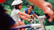 Mother smiling widely at her daugher on a bike