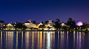 The night lights of Disney's Beach Club Resort with purple glow of Epcot's Spaceship Earth