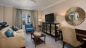 Un salón con un escritorio, sofá cama, mesa ratona, TV, armario pequeño, sillón y una ventana