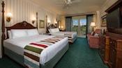 Deuxgrands lits avec tête de lit, une TV, commode, canapé-lit et, au-delà, un balcon